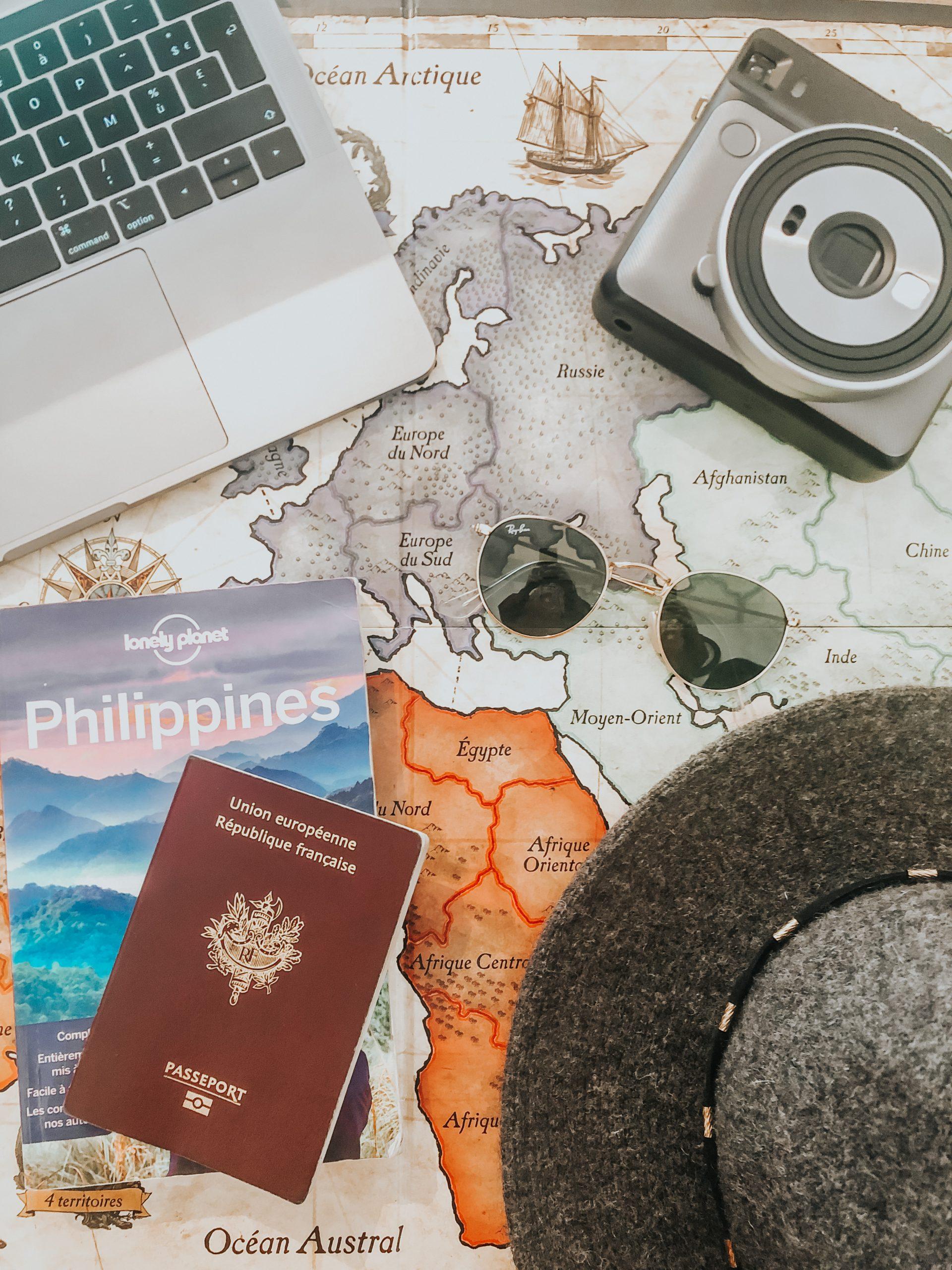 Passeport, carte du monde, ordinateur, lunettes de soleil.