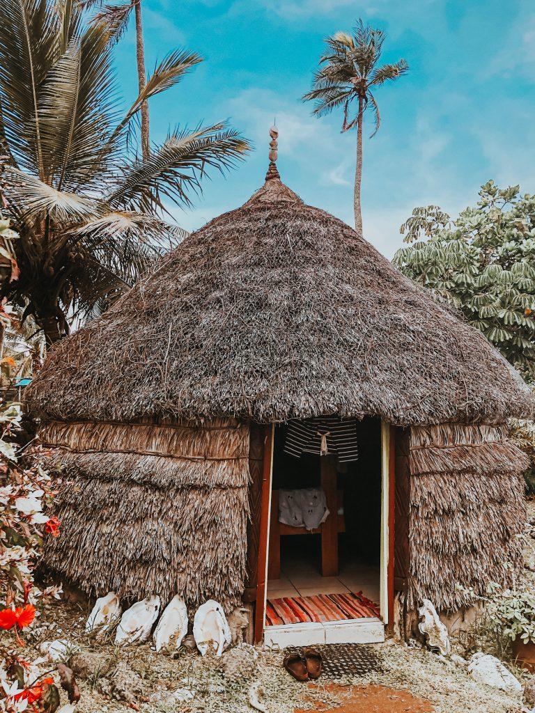 Case traditionnelle tissé en feuille de palmier, coquillages à l'entrée.