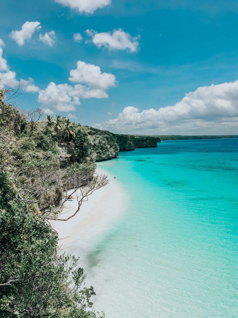 Vu à l'arrivée du chemin, vu sur la mer bleue et un banc de sable blanc au pied des falaises, kiki beach lifou