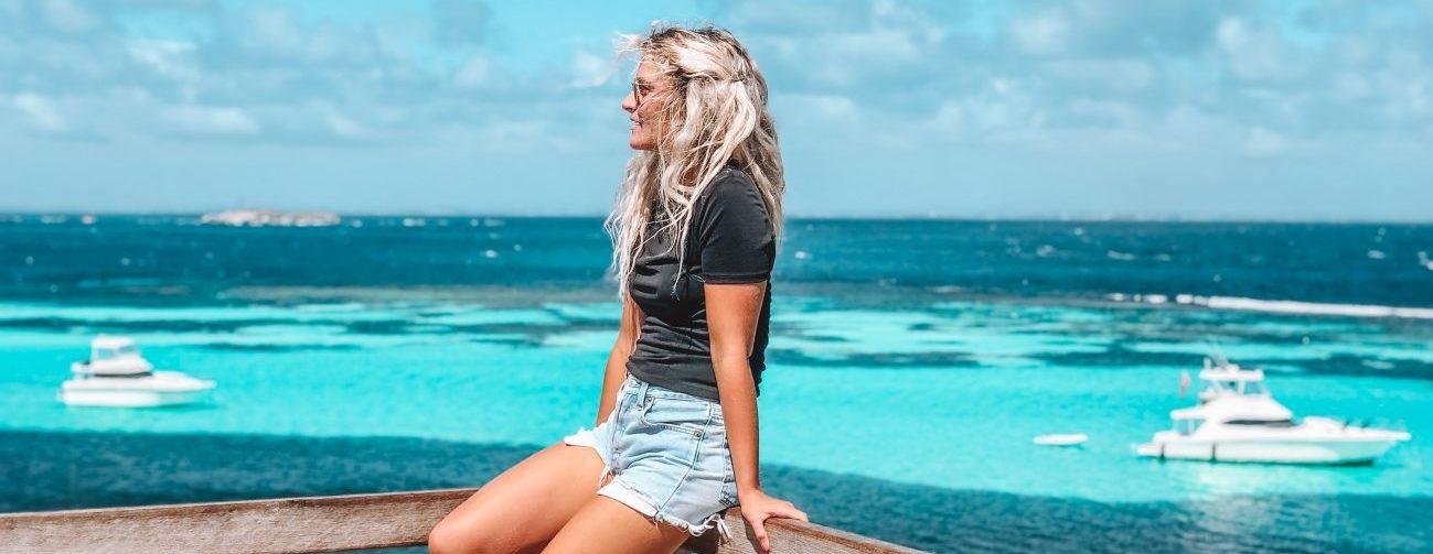 jeune femme blonde sur une rambarde devant la mer